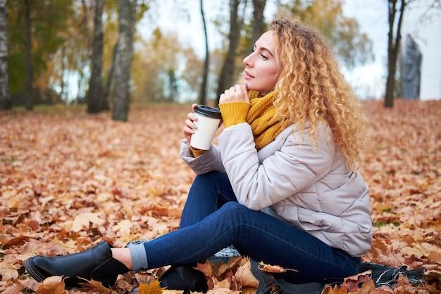 Attraente donna riccia rossa ubicazione sulle foglie d'autunno, tenendo il caffè, rilassarsi e godersi la vista del parco d'autunno