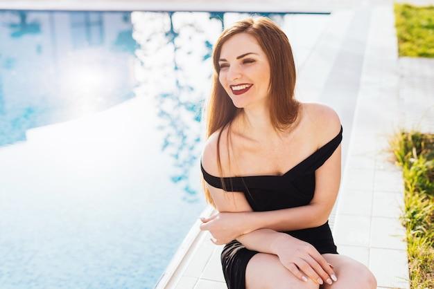 Attraente giovane donna ricca in un abito nero che riposa in piscina, ridendo al sole