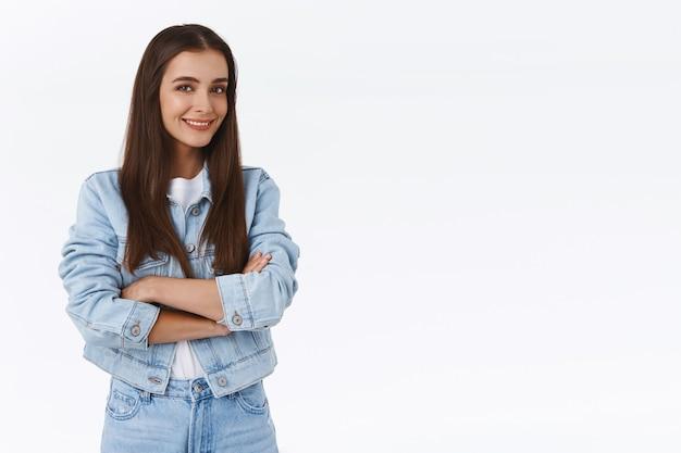 Attraente ragazza bruna impertinente in giacca di jeans, jeans, braccia incrociate sul petto, in piedi mezzo girata, guarda la telecamera entusiasta e sorridente, parlando di un interessante evento imminente