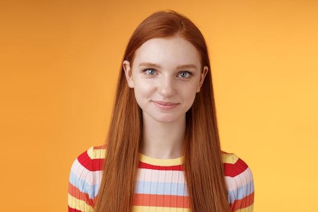 Attraente ragazza rossa sicura di sé che si incoraggia a guardare allo specchio fiducioso preparare il discorso di intervista in piedi sfondo arancione sorridendo incuriosito ascolto parlando con indifferenza.