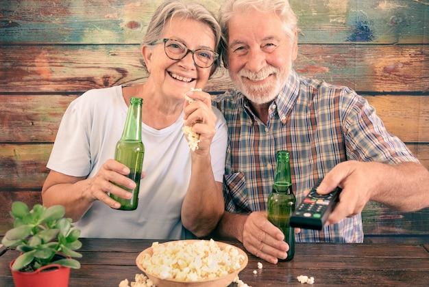 Attraente coppia senior divertirsi guardando una partita di calcio in tv, bere birra e mangiare popcorn. sfondo in legno