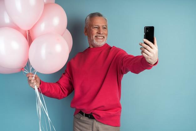 Attraente uomo anziano tiene palloncini e prende un selfie su un telefono cellulare
