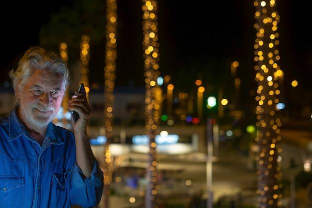 Attraente uomo anziano che usa il cellulare all'aperto di notte vicino a un albero di natale illuminato