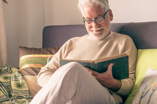 Attraente uomo anziano, capelli bianchi e occhiali, seduto sul divano di casa a leggere un vecchio libro. stile di vita rilassato per pensionati