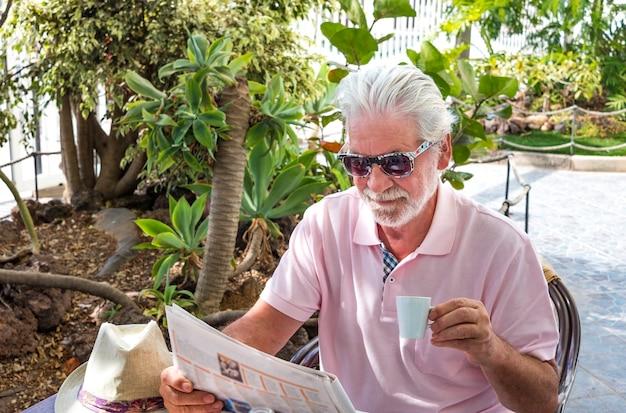 Attraente uomo anziano con occhiali da sole seduto al tavolino mentre legge il giornale e beve una tazza di caffè - intorno a lui un giardino tropicale