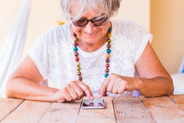 Attraente donna anziana che utilizza il telefono cellulare su un tavolo di legno
