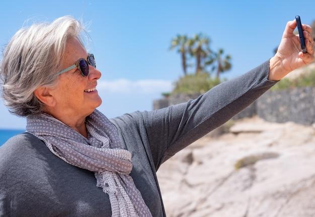 Attraente donna senior dai capelli bianchi prendendo selfie al mare sorridendo felice. concetto di stili di vita gioiosi, pensionamento felice
