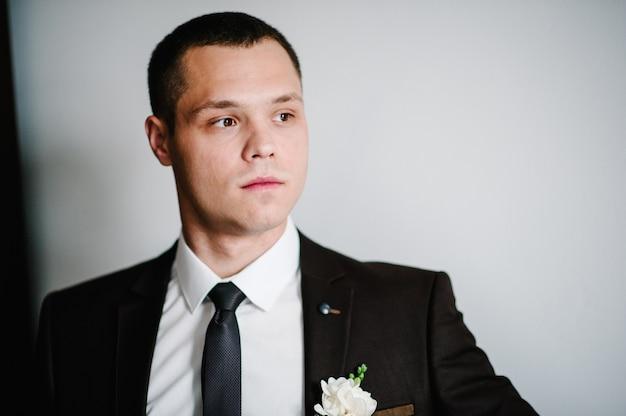 Sposo serio attraente con fiore all'occhiello in abito da sposa su sfondo bianco. l'uomo che guarda di lato.