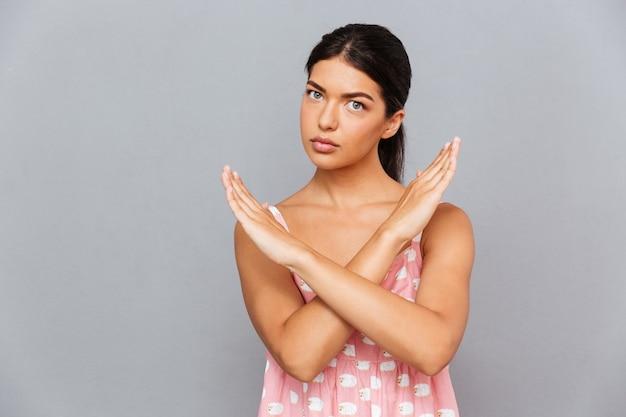 Attraente giovane donna seria in piedi con le mani incrociate e mostrando il gesto di arresto sul muro grigio