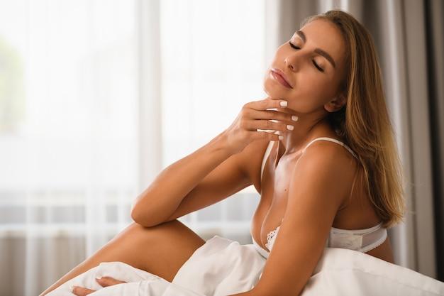 Attraente ragazza sexy si siede a letto con gli occhi chiusi, mento e collo incuranti, indossa reggiseno bianco e coperta davanti alla finestra con luce mattutina, stile di vita di lusso e tempo libero