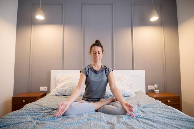 La donna invecchiata centrale sportiva di forma attraente che fa l'yoga seduta posa sul letto prima del sonno.