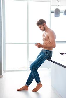 Attraente giovane a torso nudo in piedi e usa il cellulare a casa