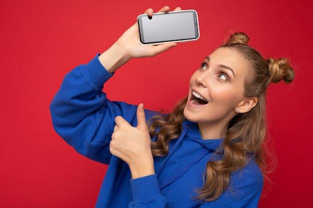 Giovane donna bionda sorridente scioccata attraente che indossa la felpa con cappuccio blu alla moda isolata sulla parete rossa