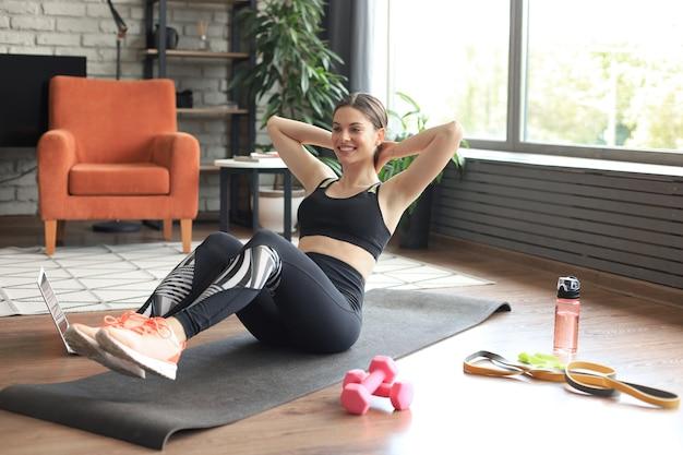 Attraente ragazza snella in abiti sportivi sta facendo esercizi addominali sul pavimento a casa. uno stile di vita sano.