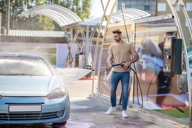 Attraente uomo magro che lava l'auto spruzzando acqua
