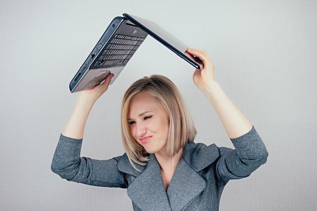 Attraente donna multitasking bionda intelligente (signora d'affari) in elegante tailleur che lavora con il computer portatile e un mucchio di cartelle arrabbiate e furiose in preda al panico in ufficio. concetto di business e scadenza