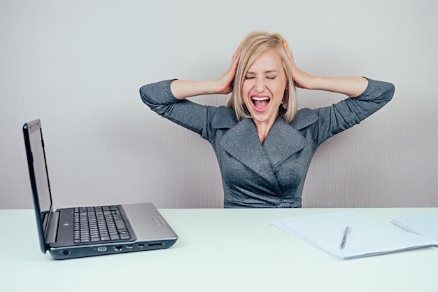 Attraente donna multitasking bionda intelligente (signora d'affari) in elegante tailleur che lavora con il computer portatile e un mucchio di cartelle urla in preda al panico in ufficio. concetto di business e scadenza