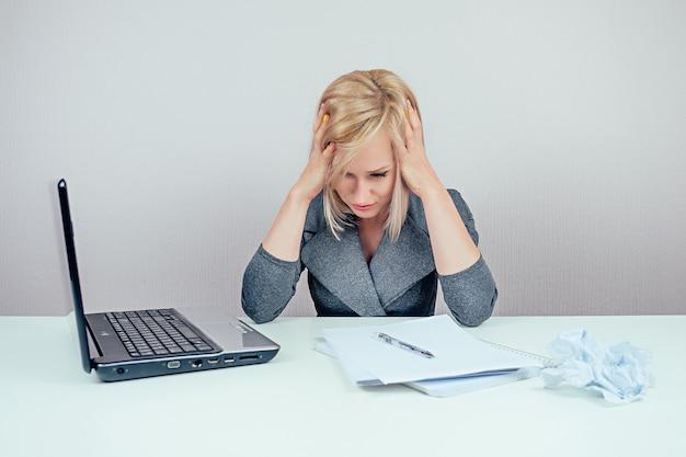Attraente donna multitasking bionda intelligente (signora d'affari) in elegante tailleur che lavora con il computer portatile e un mucchio di cartelle malate l'influenza in ufficio. concetto di quarantena e scadenza
