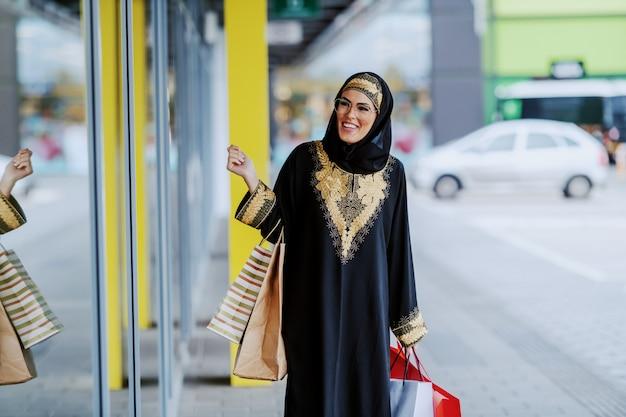 Attraente donna araba sorridente in abbigliamento tradizionale guardando la finestra del negozio in piedi con le borse della spesa in mano.