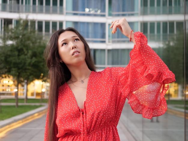 Attraente ragazza asiatica sorridente in abito rosso posa accanto alle facciate di vetro degli edifici.