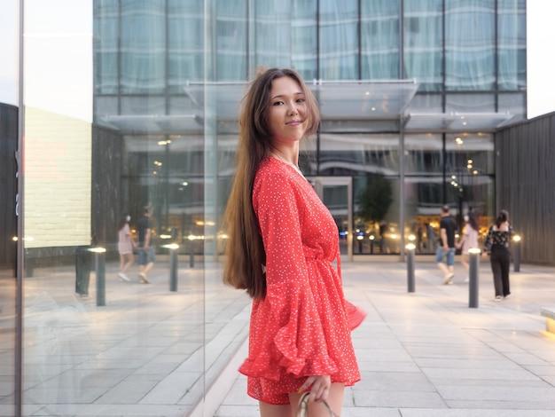 Attraente ragazza asiatica sorridente in abito rosso sorride accanto alle facciate di vetro degli edifici.