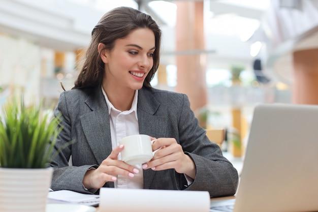 Attraente imprenditrice sorridente seduto in ufficio con una tazza di caffè.
