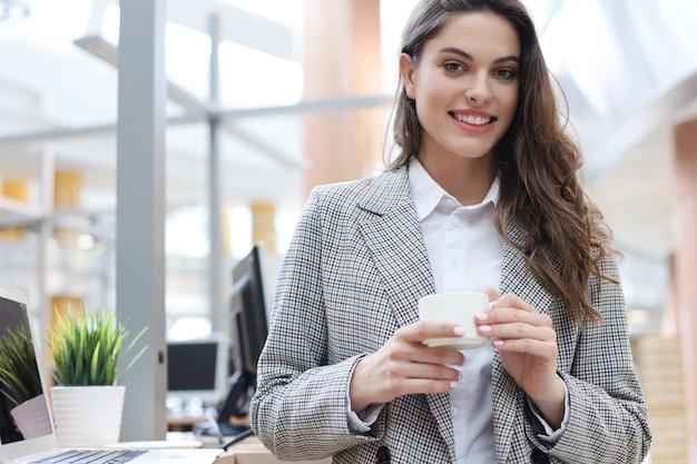 Attraente imprenditrice sorridente in piedi in ufficio con una tazza di caffè.