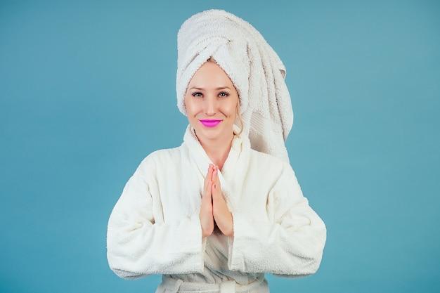 Attraente e sorridente donna calma in un accappatoio di cotone bianco e turbante asciugamano sulla testa medita in studio su uno sfondo blu copyspace. concetto di spa e relax