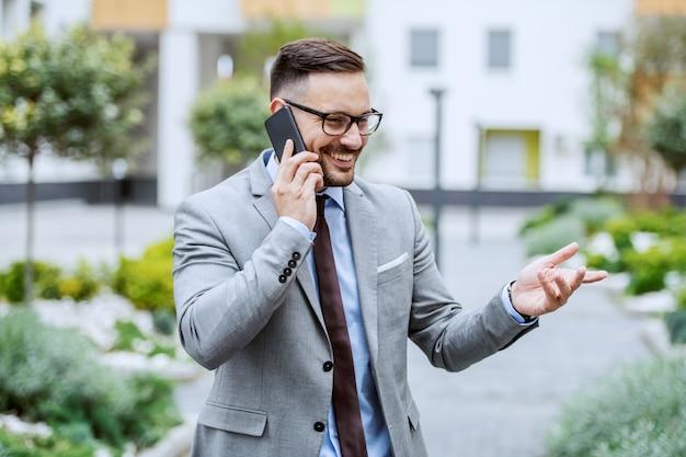 Uomo d'affari di classe caucasico sorridente attraente in vestito e con gli occhiali che parla sullo smart phone mentre stando nel parco.