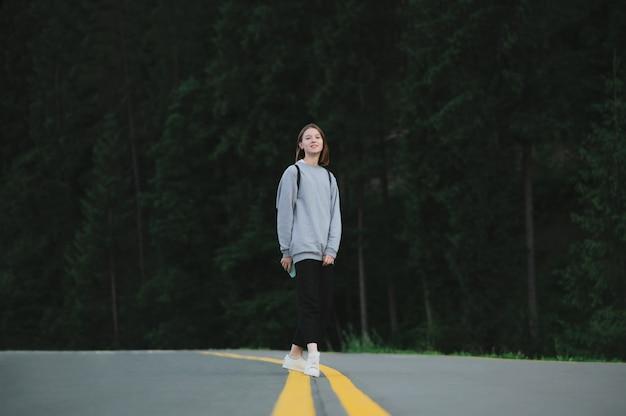 Donna turistica caucasica sorridente attraente che cammina lungo la strada asfaltata nel bosco di montagna