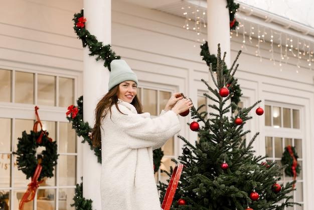 Attraente ragazza sorridente decora un albero di natale vicino alla casa