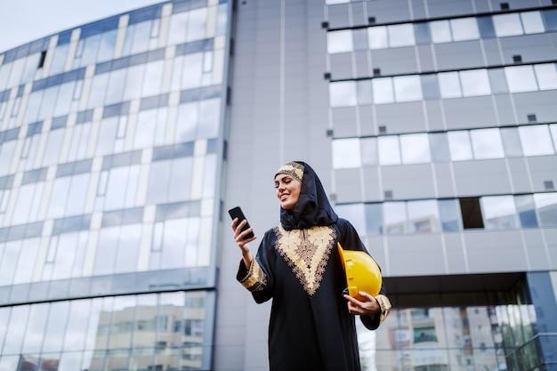 Attraente donna musulmana sorridente in piedi davanti all'edificio aziendale, utilizzando smart phone e tenendo il casco sotto l'ascella. anche le donne possono essere grandi architetti.