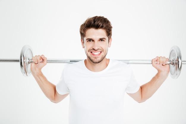 Attraente sportivo sorridente in piedi e tenendo il bilanciere
