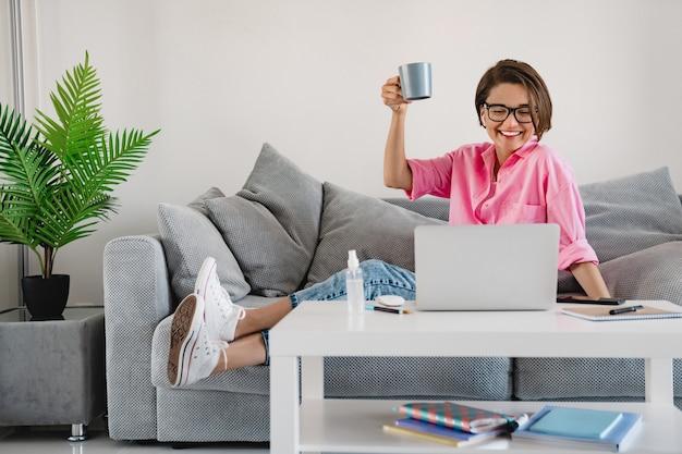 Attraente donna sorridente in camicia rosa seduta rilassata bevendo tè sul divano di casa a tavola lavorando online su laptop a casa