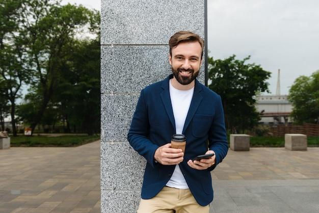 Attraente giovane uomo barbuto sorridente che indossa una giacca usando il telefono cellulare mentre si sta in piedi all'aperto in città e beve caffè da asporto