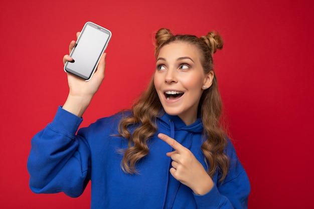 Attraente giovane donna bionda sorridente che indossa elegante felpa con cappuccio blu isolato su sfondo rosso con