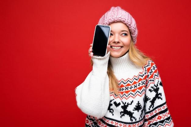 Attraente giovane donna bionda sorridente che indossa un caldo berretto lavorato a maglia e un maglione caldo invernale