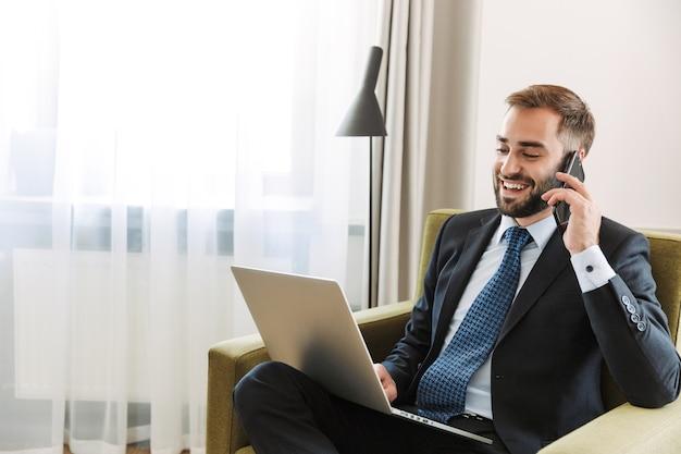 Attraente giovane uomo d'affari sorridente che indossa un abito seduto su una sedia nella camera d'albergo, lavorando su un computer portatile