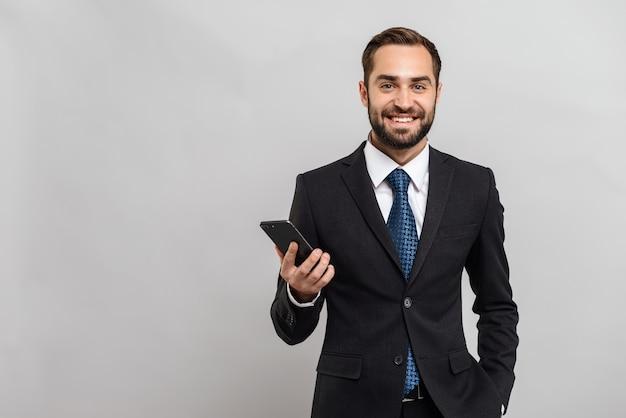 Attraente giovane uomo d'affari sorridente che indossa un abito in piedi isolato su un muro grigio, con in mano un telefono cellulare