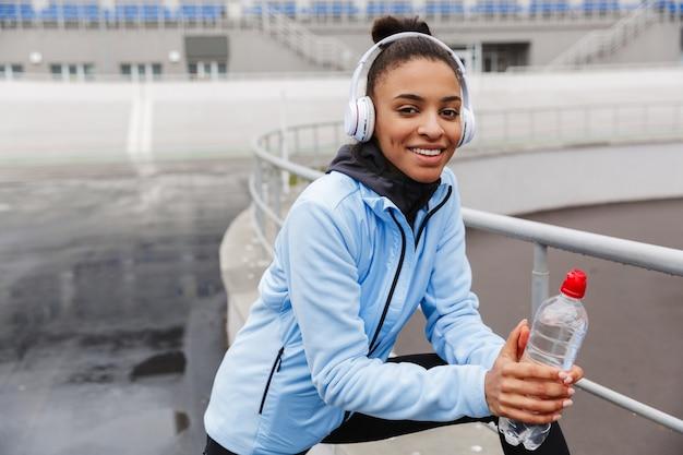 Attraente giovane sportiva africana sana e sorridente che ascolta musica con auricolari wireless che si sforzano allo stadio, tenendo in mano una bottiglia d'acqua