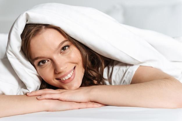 Attraente giovane donna sorridente sdraiata a letto sotto le coperte a casa