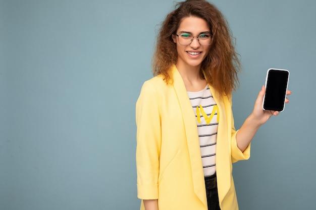 Attraente giovane donna sorridente con capelli biondi scuri ricci che indossa giacca gialla e occhiali ottici