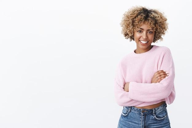 Attraente donna afroamericana socievole e carismatica anni '20 con i capelli biondi ricci in un caldo maglione invernale che si tiene con le mani incrociate sul corpo e sorride felice sentendosi felice e gioiosa
