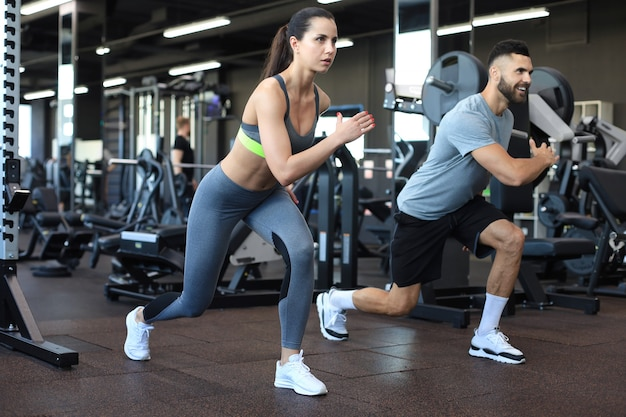 Attraente coppia sportiva facendo fitness in palestra.