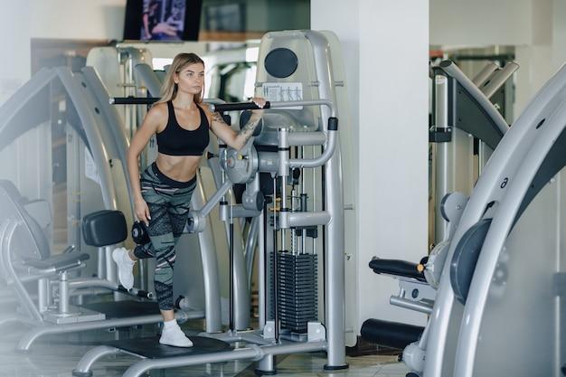 Attraente ragazza sportiva si esercita su fianchi e glutei. uno stile di vita sano.