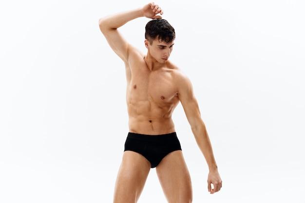 Uomo attraente di sport in pantaloncini scuri su un bodybuilder di sfondo chiaro