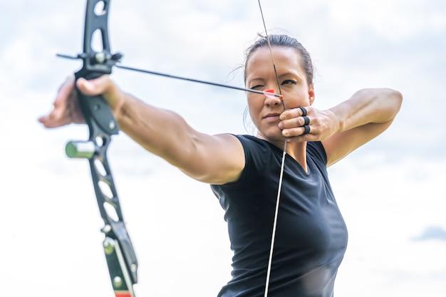 Attraente donna sportiva in tiro con l'arco, frecce e arco in azione