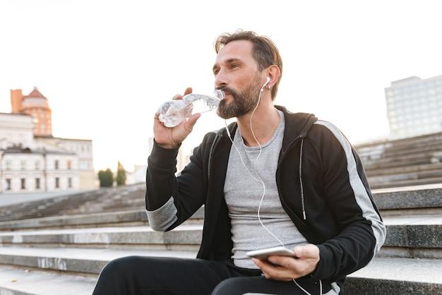 Sportivo attraente in auricolari tenendo il telefono cellulare