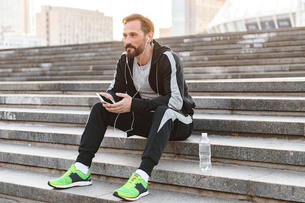 Attraente sportivo in auricolari utilizzando il telefono cellulare