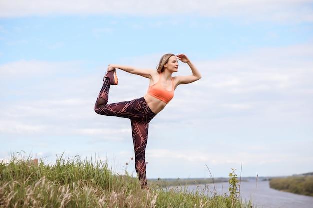 La sportiva attraente sta praticando lo yoga sulla sponda del fiume